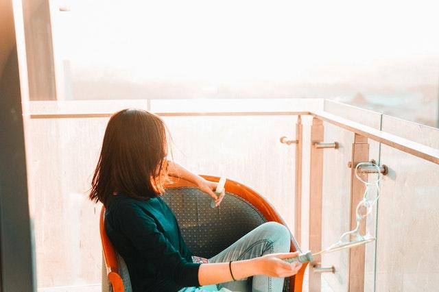 Žena s bublifukom v ruke sedí na balkóne so skleneným zábradlím počas západu slnka