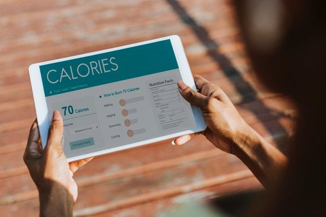 Žena drží v rukách tablet so stránkou o kalóriách