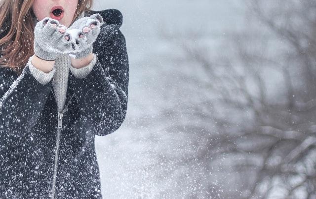Žena v rukaviciach v zimnej bunde fúka do snehu.jpg
