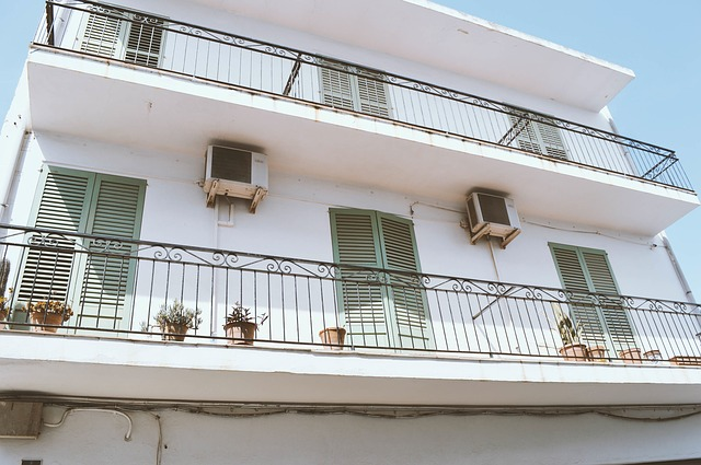 Biela budova s veľkým podlhovastým balkónom so zábradlím.jpg