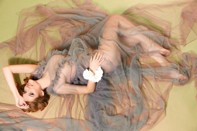 Nahá žena zahalená v priesvitnej látke